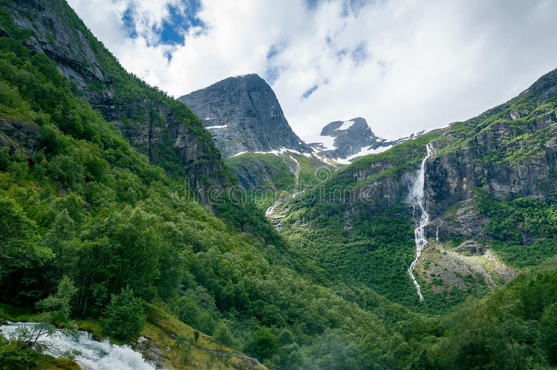 Dreamy norwegian mountain valley. Dreamy mountain valley with green forests, rocks and waterfalls. Hiking path to Briksdalsbreen glacier. Briksdal, Norway stock photos