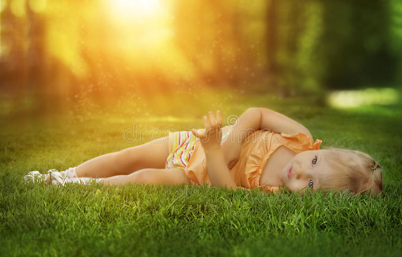 Dreamy photo of a little girl in the grass. Surrealistic photo of a little girl in the grass stock image