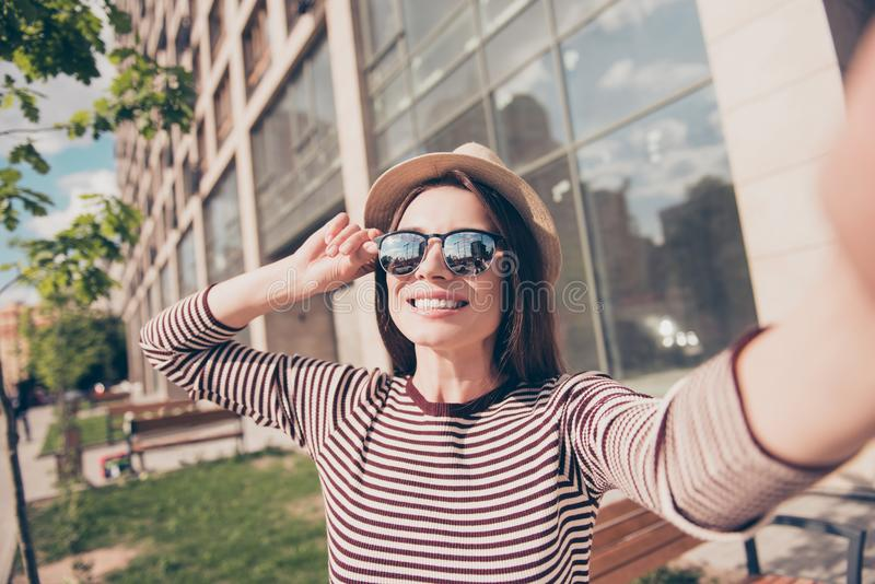 Dreamy relaxed young girl is making selfie shot on camera while walking in the spring sunny city outdoors, smiling, in casual comf royalty free stock photography