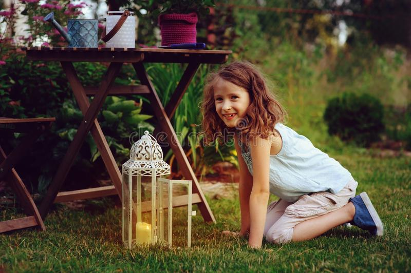 Dreamy romantic kid girl relaxing in evening summer garden. Decorated with lantern and candle holder lights stock photos