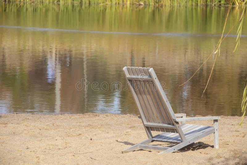 Dreamy scene of wooden beach chair in sand with reflections of reeds in water and willow branches on side - selective focus royalty free stock photo