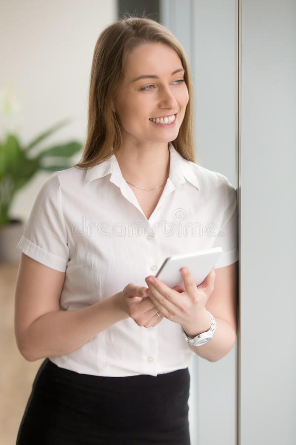 Dreamy smiling businesswoman holding digital tablet looking away. Dreamy happy businesswoman holding digital tablet computer while standing at home office stock images