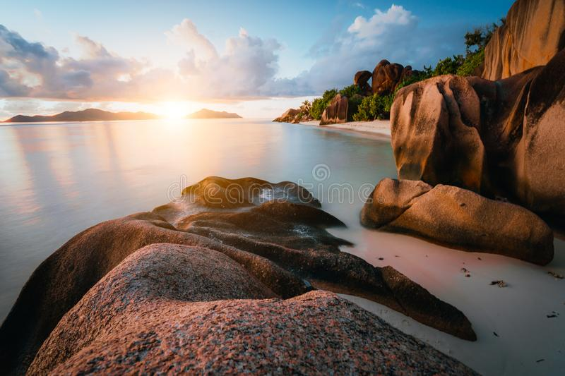 Dreamy sunset at the gorgeous exotic Anse Source d`Argent beach, La Digue island, Seychelles. Long exposure panorama stock photo