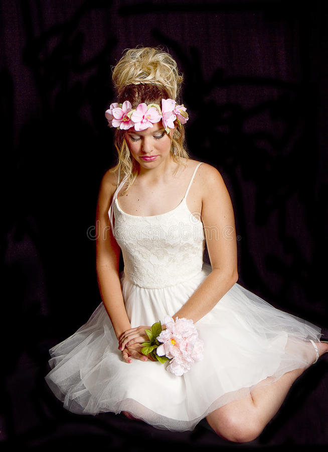Dreamy Teen Blonde Girl - Party Dress - Sitting. Pretty blonde teen girl wearing a white party dress while sitting holding flowers. She has a crown of pink stock photo