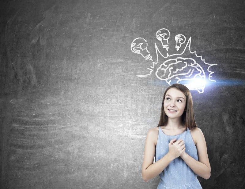 Dreamy teen girl with hands near heart, brain bulb royalty free stock image