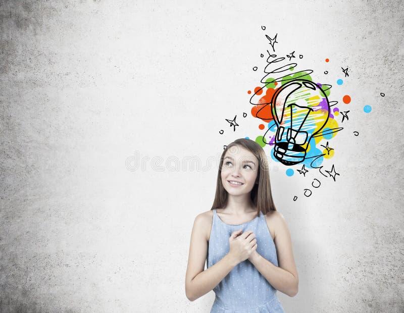 Dreamy teen girl with hands near heart, light bulb royalty free stock photo