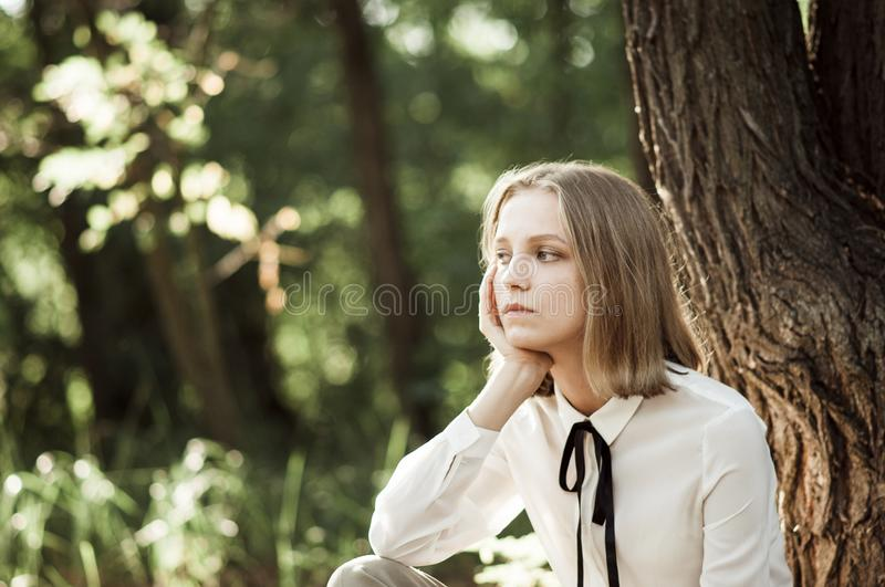 Dreamy teen girl in white blouse with black ribbon. Behind the bark in the forest stock photos