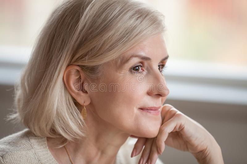 Dreamy thoughtful mature woman relaxing hoping thinking of happy royalty free stock image