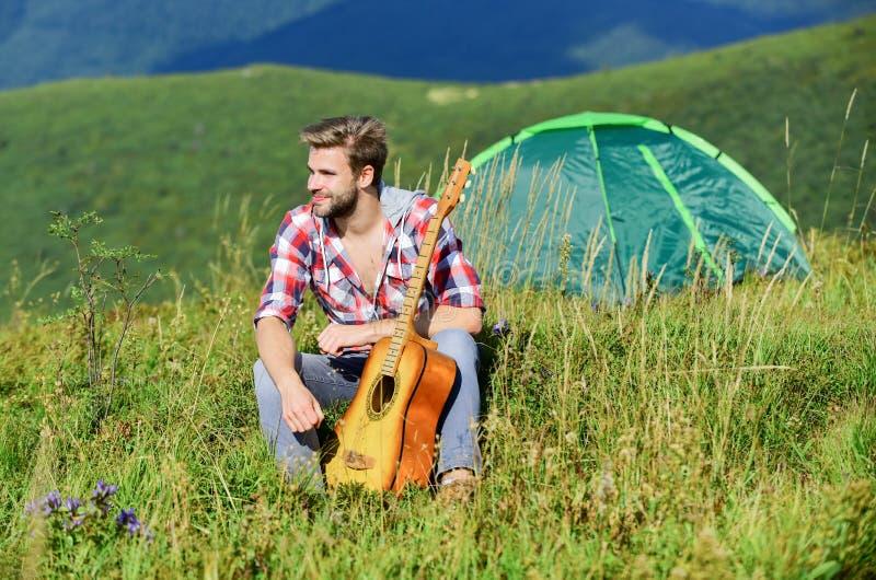 Dreamy Wanderer Tempo agradável sozinho Humor pacífico Guy com guitarra contemplando a natureza Conceito de wanderlust Inspiração fotografia de stock
