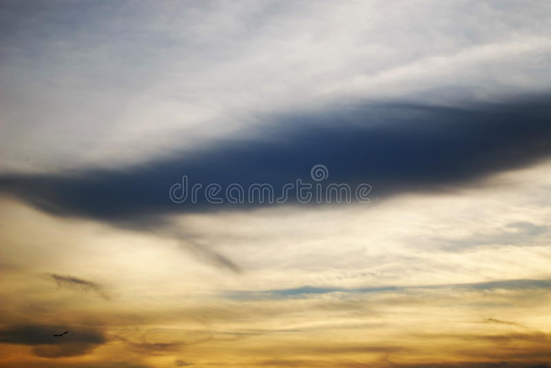 Dreamy waves. Still dreamy clouds looks like a still tornado in the light yellow sky stock images