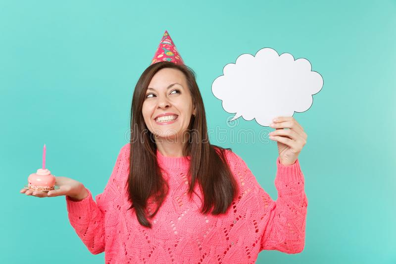 Dreamy woman in birthday hat looking up holding cake with candle, empty blank Say cloud speech bubble for promotional. Content isolated on blue background stock image