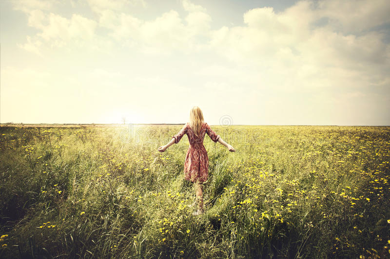 Dreamy woman walking in nature towards the sun stock photography