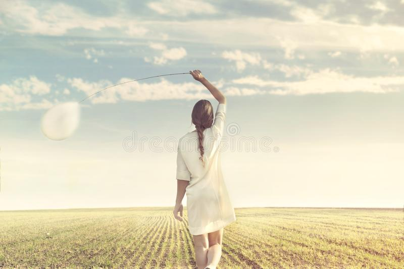 Dreamy woman walking towards infinity with her white balloon royalty free stock images