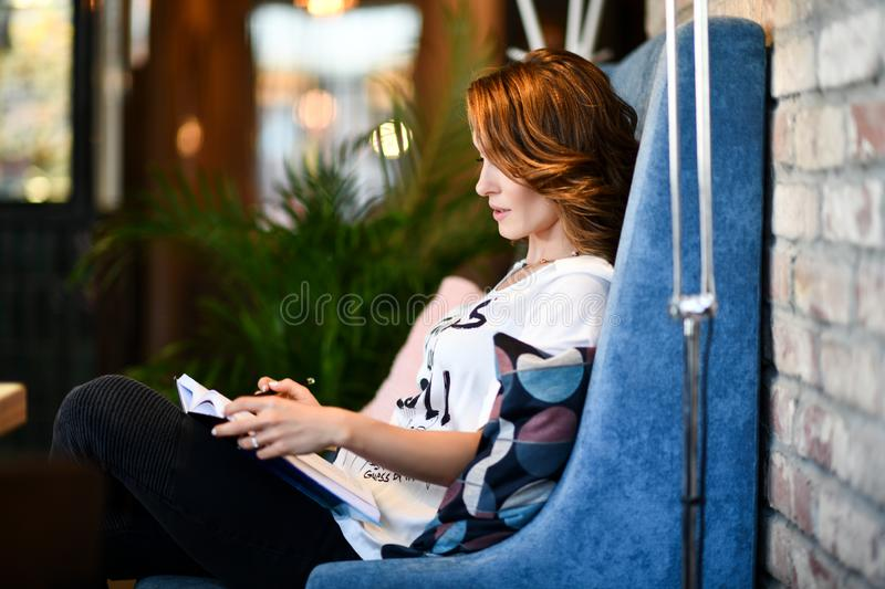 Dreamy young beautiful woman writes future plans and goals in her diary, relaxing in a cozy dining room reading a book royalty free stock photo