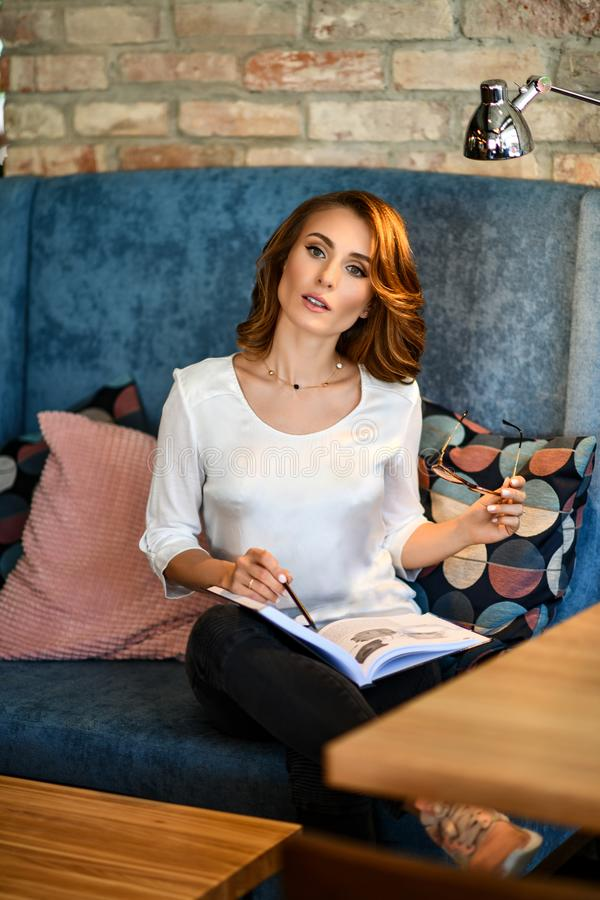 Dreamy young beautiful woman writes future plans and goals in her diary, relaxing in a cozy dining room reading a book. stock photography