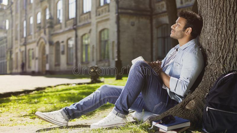 Dreamy young male sitting with notebook under tree, thinking what to write, idea stock photography