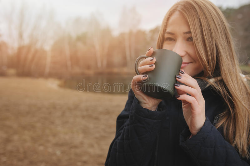 Dreamy young woman drinking hot tea outdoor on the walk, enjoying traveling in autumn. Weekend stock image
