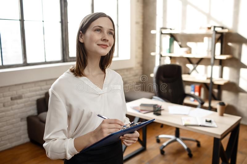 Dreamy young woman stand in room aloone and look up. She write and smile. Empty room. Daylight. stock image
