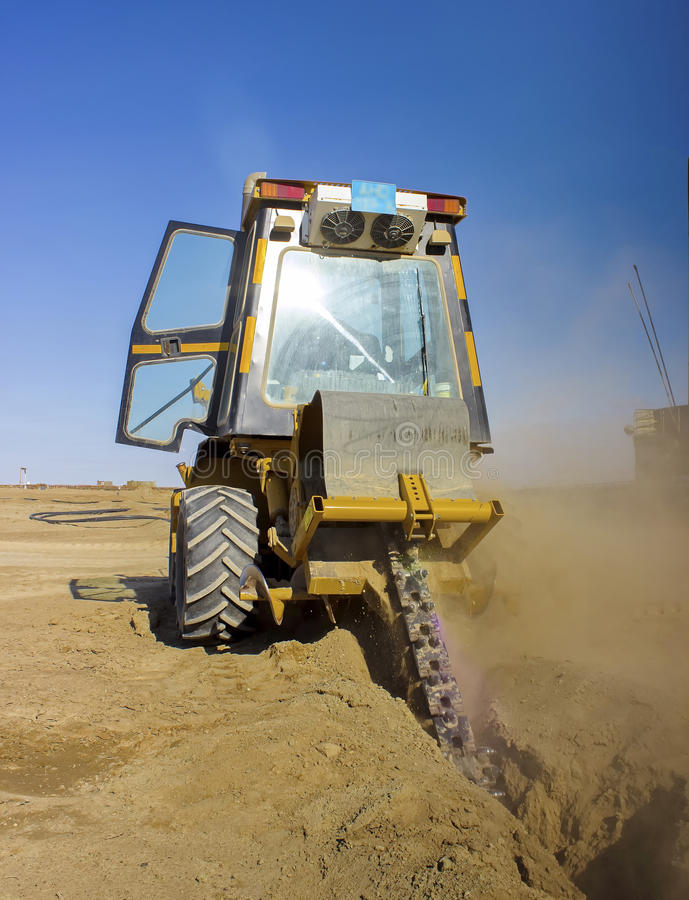 Dredge. Climbs into the ground trench for laying communications Betpakdala steppe, southern Kazakhstan stock photos