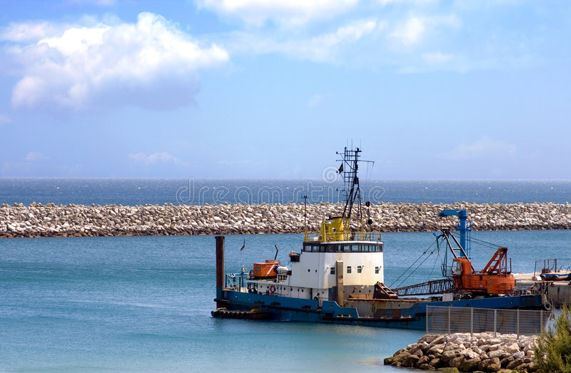 Dredge at the Harbor. Dredge anchored at the harbor under a beautiful cloudy sky royalty free stock photography