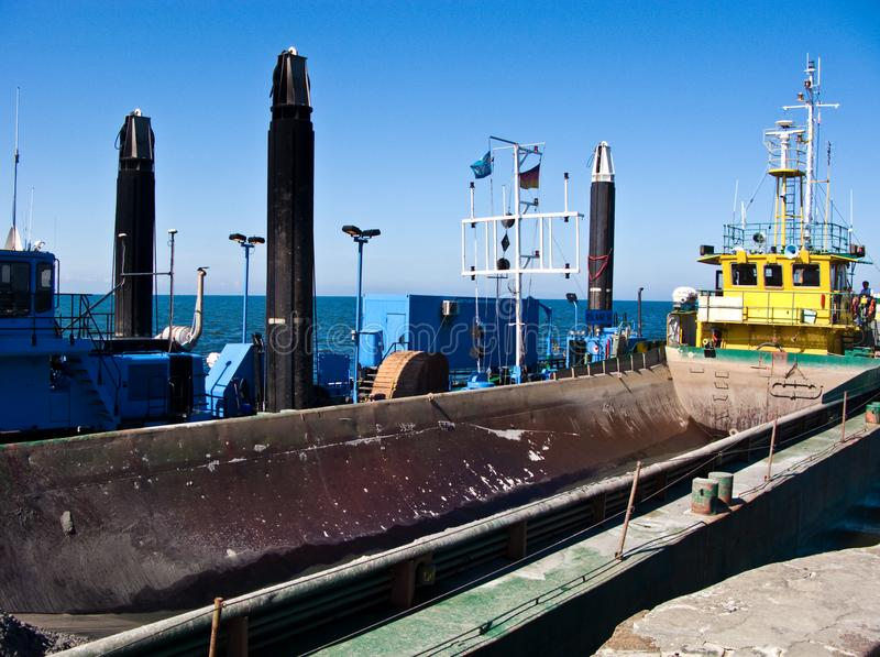 Dredger ship at work in Baltic port entrance royalty free stock image