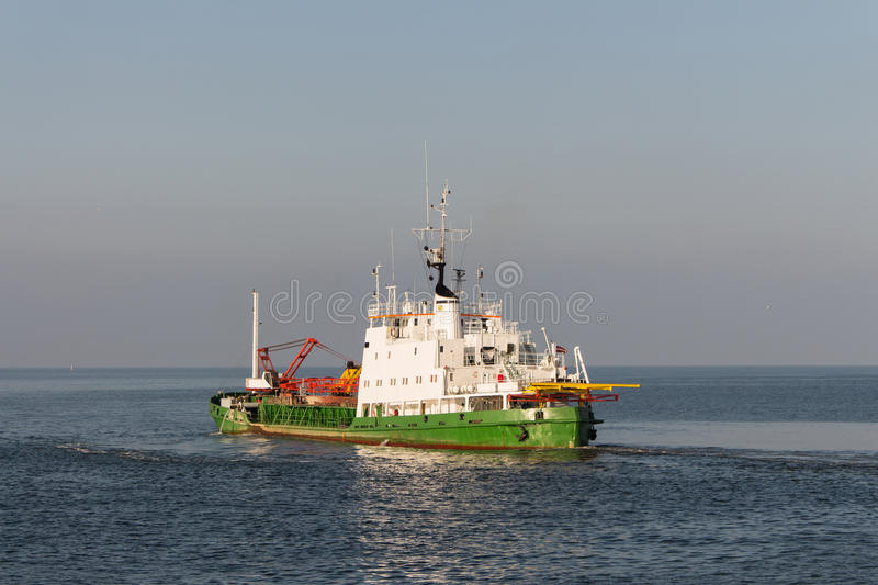 Dredger Vessel in beautiful weather leaving the port of Ventspils.  royalty free stock photos