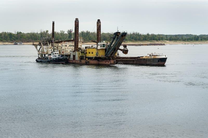 Dredging platform and cargo ship stock images