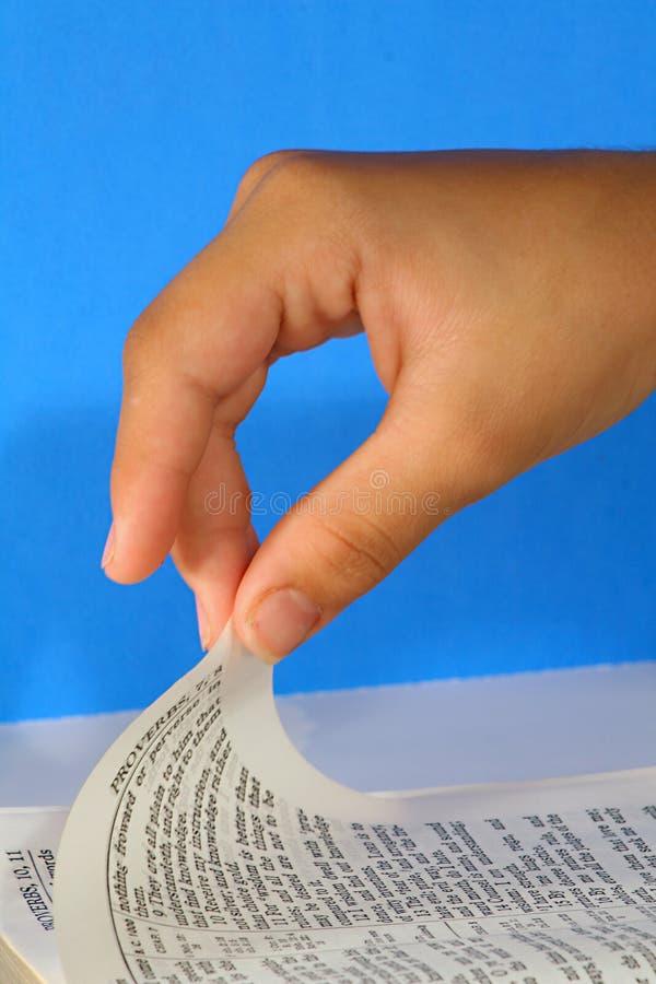 Drehen die Seite einer Bibel auf Blau - Sprichwörter stockfotografie