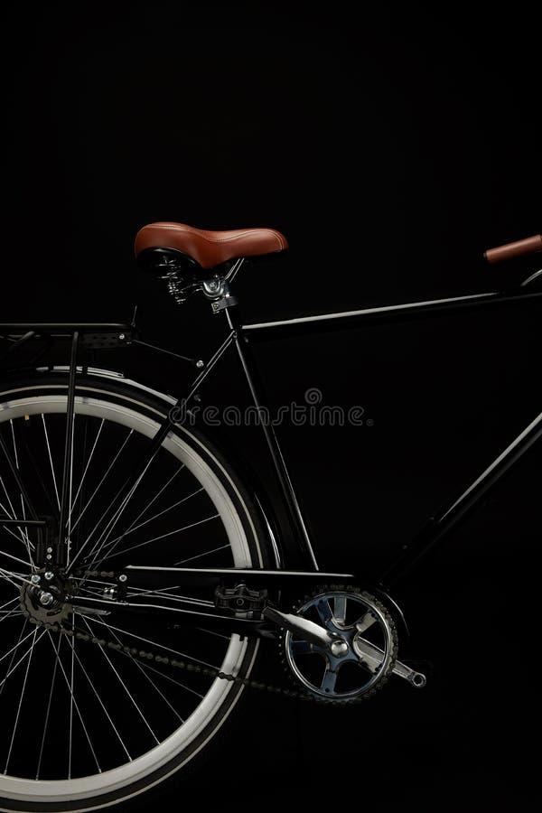 drehen Sie sich, der Sattel und Pedale des klassischen Fahrrades lokalisiert auf Schwarzem stockfotografie