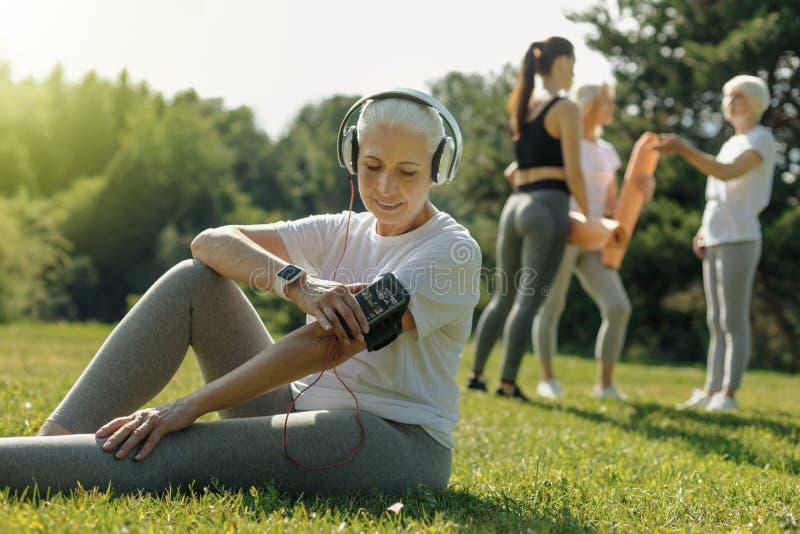 Drehenmusik entspannter älterer Dame vor Training lizenzfreie stockfotografie
