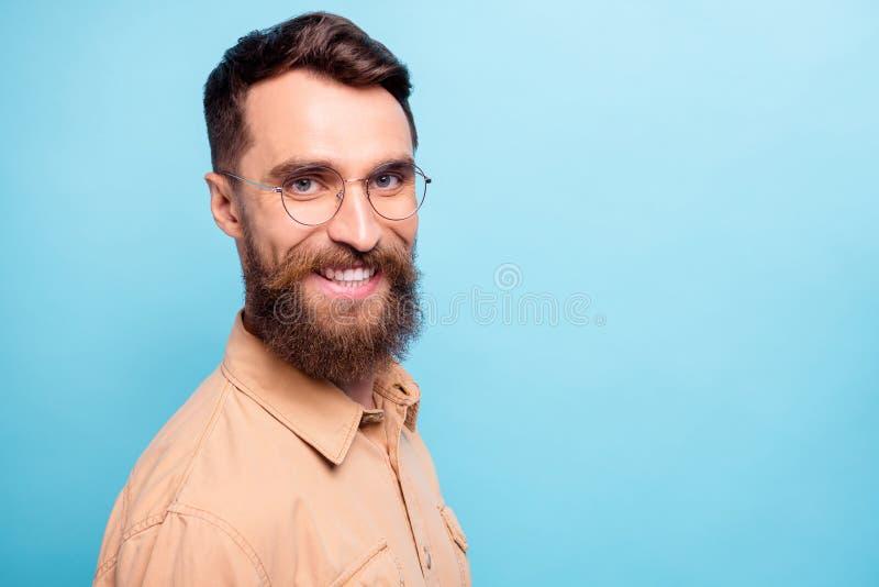 Drehtes Foto des charmanten Mannes mit leuchtendem Lächeln über blauem Hintergrund mit braunem Hemd lizenzfreie stockfotos