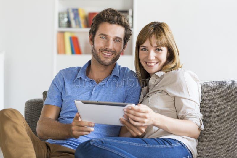 Dreißig jährige Paare auf APP tablet PC im modernen weißen Haus lizenzfreies stockbild