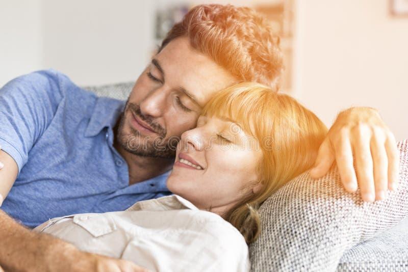 Dreißig jährige Paare, die auf Sofa sich entspannen Augen geschlossen stockfoto