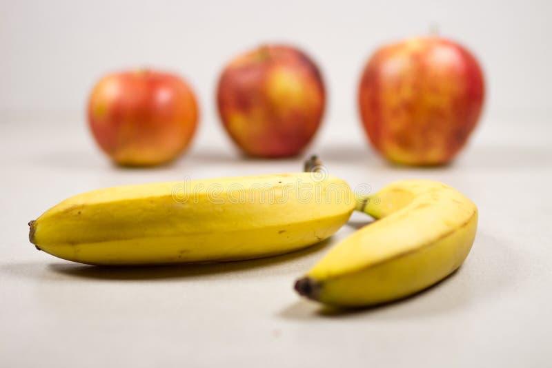 Drei Äpfel und zwei Bananen auf einem Gray White Grey Marble Slate-Hintergrund stockfotos