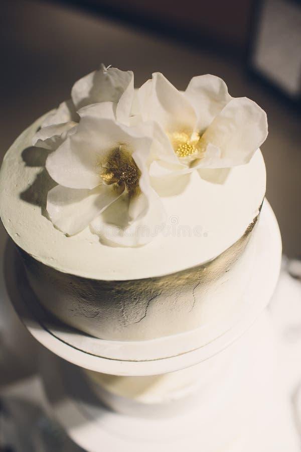 Drei-abgestufte wei?e Hochzeitstorte verziert mit Blumen vom Mastix auf einem wei?en Holztisch Bild f?r ein Men? oder ein a stockfotografie