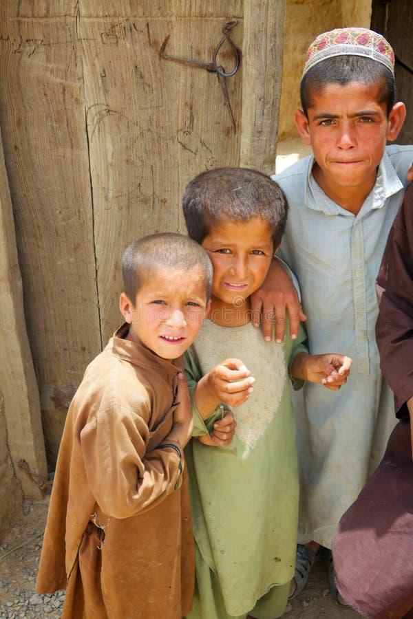 Drei afghanische Kinder passen eine ISAF-Patrouille auf stockbild