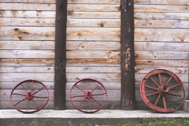 Drei alte Räder zu einem Warenkorb auf dem Hintergrund einer hölzernen hölzernen Turmwand auf einem Beton lizenzfreies stockbild