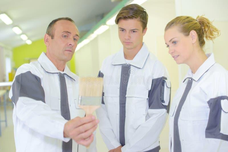 Drei Arbeitskräfte, die neuen Malerpinsel betrachten stockfoto