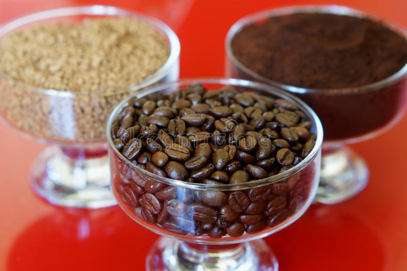 Drei Arten Kaffee in den Glasschüsseln auf einem roten Hintergrund: gebratene Bohnen, Boden, sofortig stockfoto
