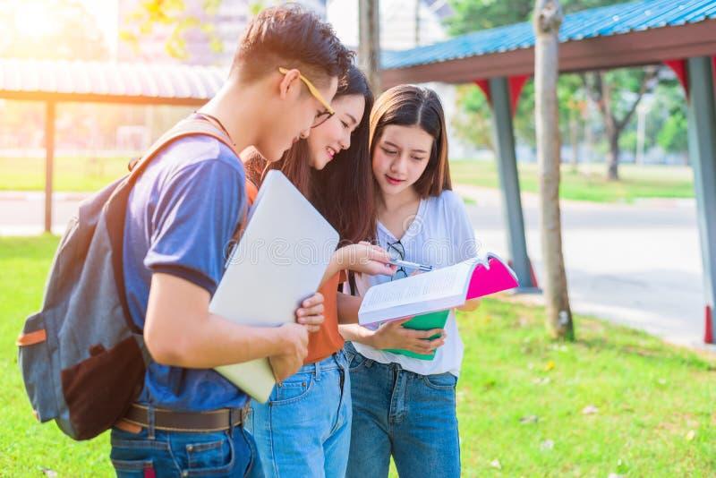Drei asiatische junge Campusleute, die für Schluss unterrichten und sich vorbereiten stockfotografie