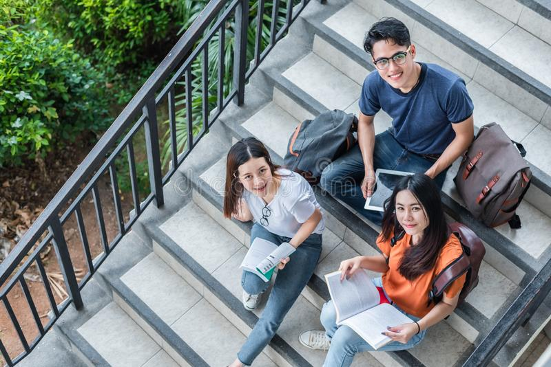Drei asiatische junge Campusstudenten genie?en, an der Bibliothekstreppe zusammen zu unterrichten und Ablesenb?cher Freundschafts lizenzfreies stockfoto