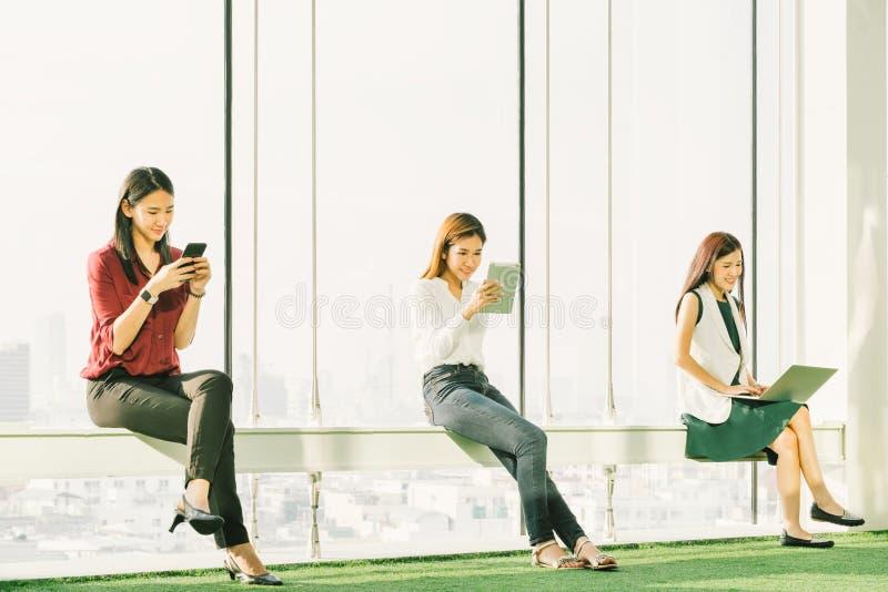 Drei asiatische Mädchen, die digitale Tablette des Smartphone und Laptop-Computer im modernen Büro bei Sonnenuntergang verwenden  lizenzfreie stockfotos