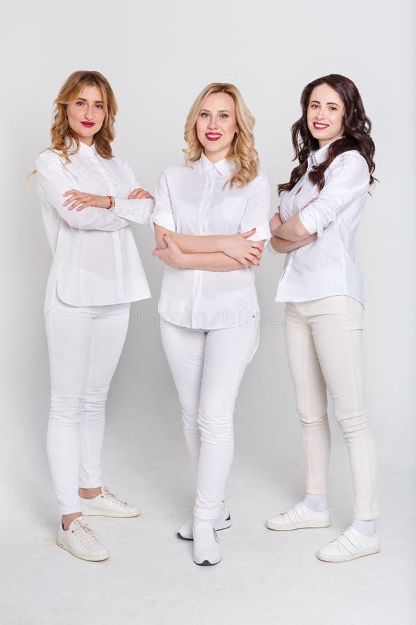 Drei attraktive Frauen im weißen Porträt auf weißem Hintergrund lizenzfreie stockfotografie