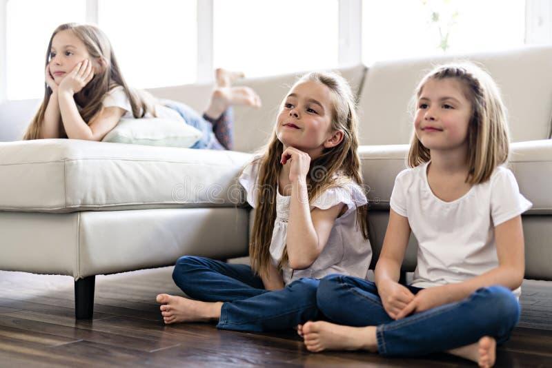 Drei attraktive Jugendlichen in der zufälligen Kleidung zu Hause fernsehend stockfoto