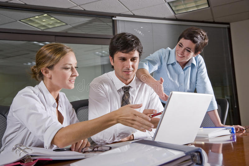 Drei Büroangestellte, die im Sitzungssaal arbeiten stockbilder