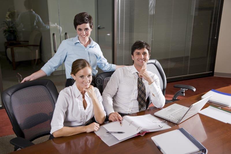 Drei Büroangestellte, die im Sitzungssaal arbeiten lizenzfreies stockbild