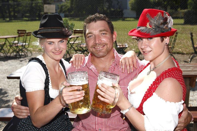 Drei Bayern in den traditionellen Kostümen, die in einem Bier sitzen, arbeiten im Garten stockbild