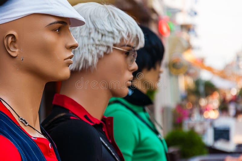 Drei bemannt, Mannequins in der unterschiedlichen Kleidung, die auf erstem Reihenstraßenmeer steht, promenieren voll von gehenden stockfoto