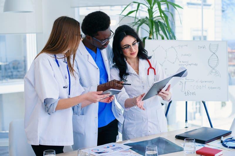 Drei Berufsdoktoren überprüfen den Röntgenstrahl eines Patienten Zwei Frauendoktoren und ein männliches Doktorzusammenarbeitung a stockfotos