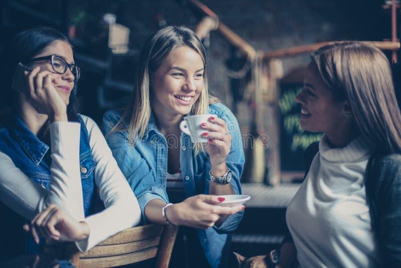 Drei beste Freundinnen, die im Café sprechen lizenzfreie stockfotos
